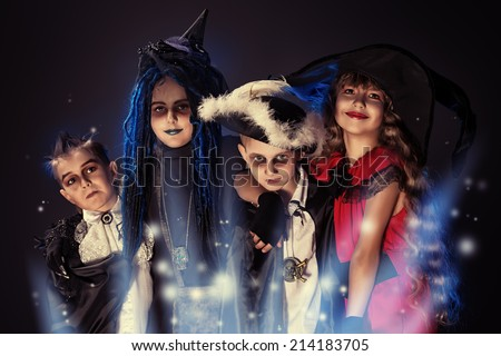 Cheerful children in halloween costumes posing over dark background.