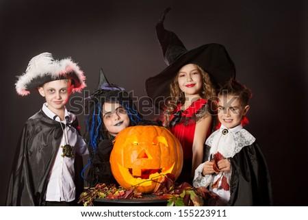 Cheerful children in halloween costumes posing with pumpkin. Over dark background. - stock photo