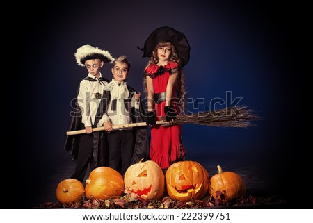 Cheerful children in halloween costumes standing with pumpkins and a broom. Over dark background. - stock photo