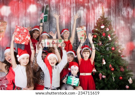 Cheerful children in santa cluas hats holding Christmas presents