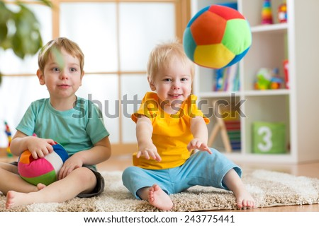 cheerful children playing with ball in playroom - stock photo
