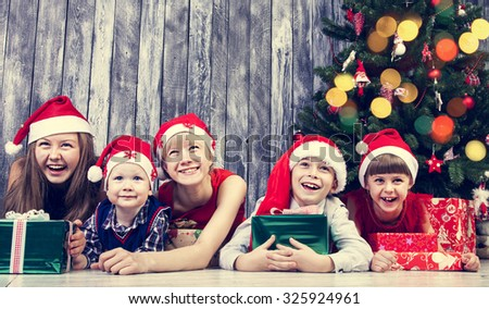 Cheerful children with gifts next Christmas tree  - stock photo