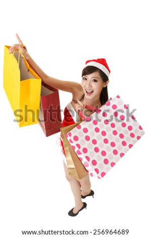 Cheerful Christmas lady holding shopping bags and smiling, full length portrait isolated on white background.