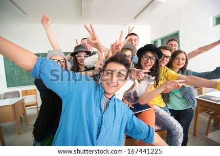 Cheerful classmates posing in classroom in front of a green board - stock photo