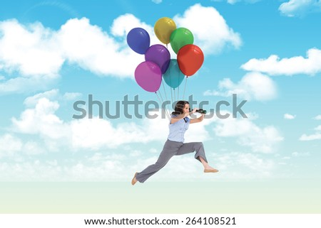 Cheerful classy businesswoman jumping while holding binoculars against blue sky - stock photo