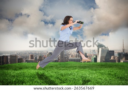 Cheerful classy businesswoman jumping while holding binoculars against cloudy sky over city - stock photo