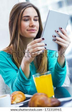 Cheerful classy woman using tablet while having breakfast in coffee shop - stock photo