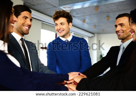 Cheerful co-workers making pile of hands and looking at each other - stock photo