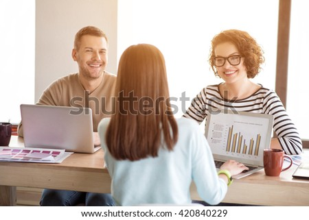 Cheerful colleague working at the table
