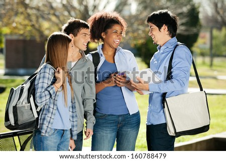 Cheerful college students looking at male friend in campus - stock photo