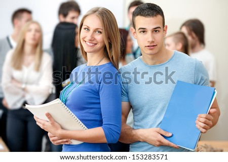 cheerful college students with books with group of students in background  - stock photo