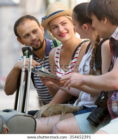 Cheerful company of impressed travelers during city walking. Focus on woman with red lipstick - stock photo