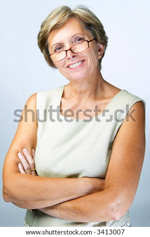 Cheerful confident mid adult woman with her arms crossed, studio shot - stock photo