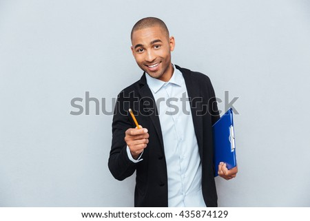Cheerful confident young businessman holding clipboard and pencil - stock photo