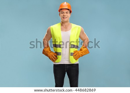 Cheerful construction worker posing and smiling on a blue background - stock photo