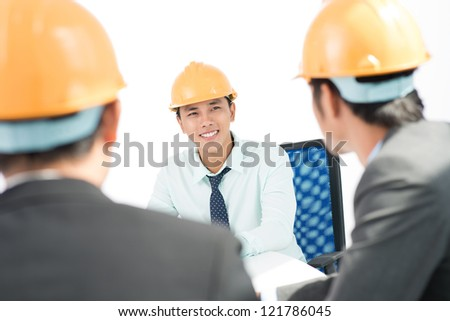 Cheerful contractor being satisfied with the results of the meeting with his colleagues - stock photo