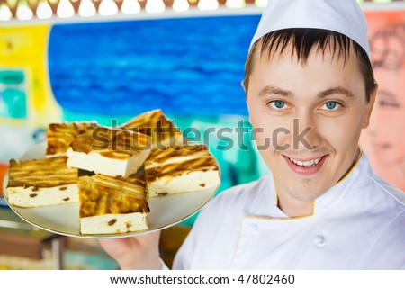 cheerful cook in uniform holding cheese baked pudding on dish - stock photo