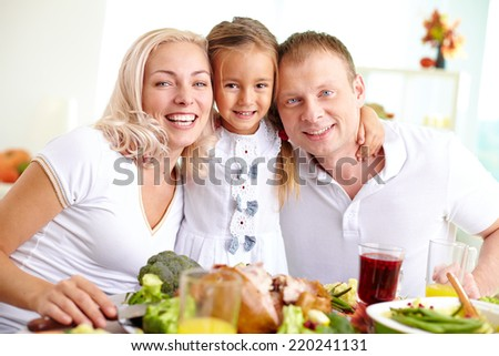Cheerful couple and their daughter looking at camera at Thanksgiving dinner - stock photo