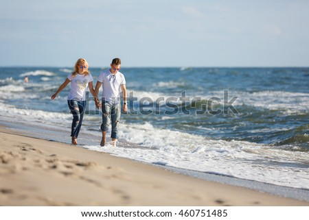 Cheerful couple are walking on the beach, summer time