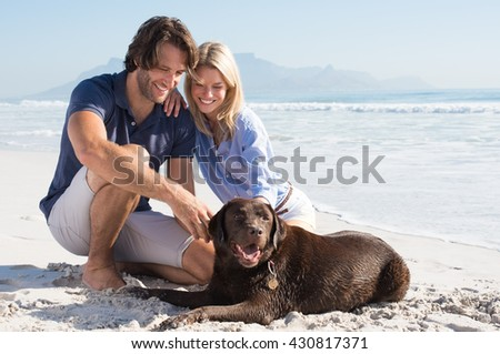 Cheerful couple at beach playing with labrador retriever. Couple relaxing at beach with their pet. Happy couple with their dog at the beach on a sunny day. - stock photo