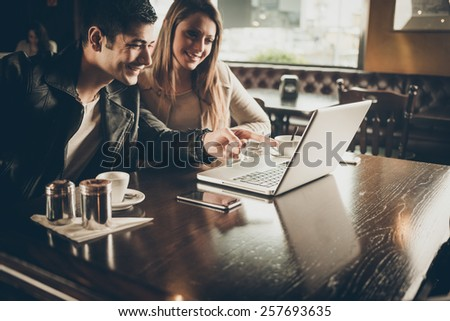 Cheerful couple at the cafe with a computer, he is pointing at the laptop screen - stock photo