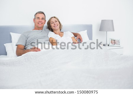 Cheerful couple cuddling in bed looking at camera at home in bedroom - stock photo