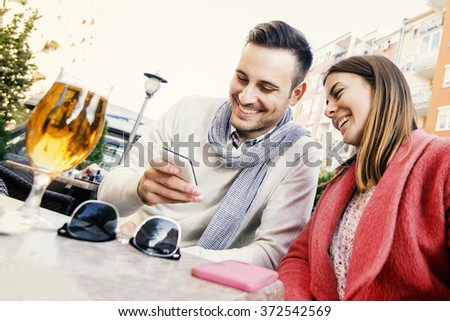 Cheerful couple drinking beer outdoors. They are laughing and having a great time. - stock photo