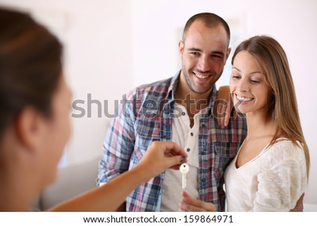 Cheerful couple getting keys of their new home - stock photo