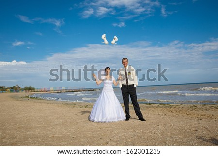 Cheerful couple  groom and bride throw shoes