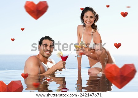 Cheerful couple having cocktails in the pool against hearts - stock photo