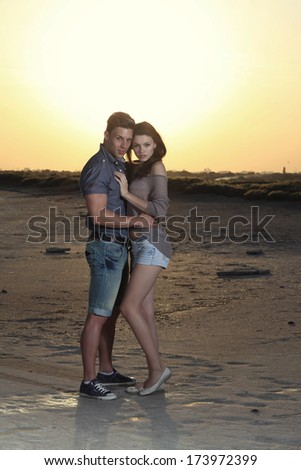 Cheerful couple having fun on summer vacation.Portrait of a beauty young couple in love having holidays on the sea. Fashion colors