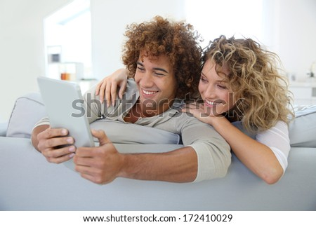 Cheerful couple having fun using tablet in sofa - stock photo