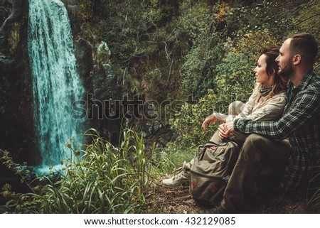Cheerful couple hikers sitting near waterfall in deep forest.