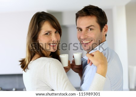 Cheerful couple holding cups of coffee - stock photo