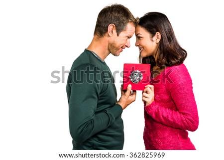 Cheerful couple holding gift box on white background - stock photo