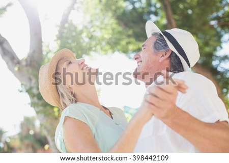 Cheerful couple holding hands against trees - stock photo