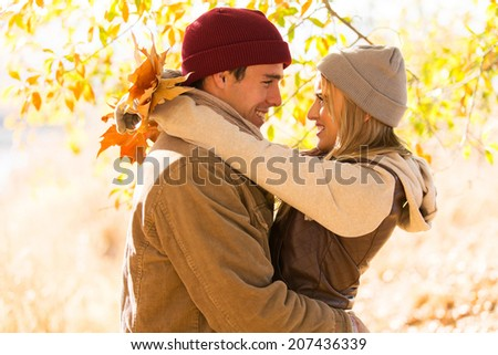 cheerful couple hugging in autumn park - stock photo