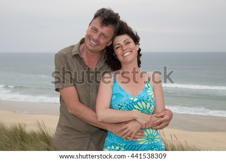 Cheerful couple hugging on the beach on a holidays