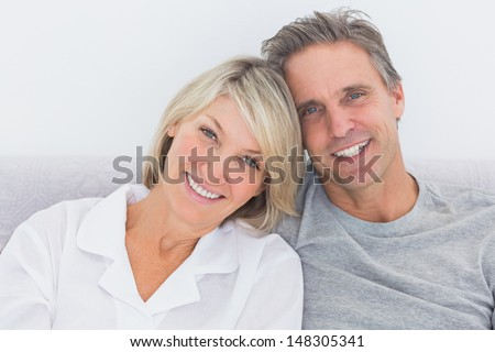 Cheerful couple in bed smiling at camera - stock photo
