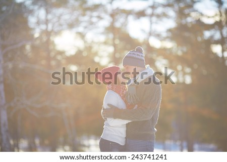 Cheerful couple in knitted winterwear embracing outdoors - stock photo