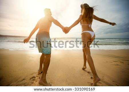 cheerful couple in love run on the beach and holding hands - stock photo