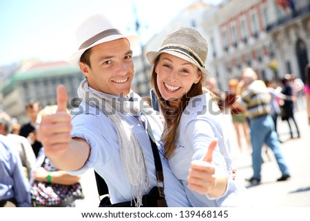 Cheerful couple in Madrid showing thumbs up - stock photo
