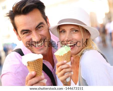 Cheerful couple in Rome eating ice cream cones - stock photo