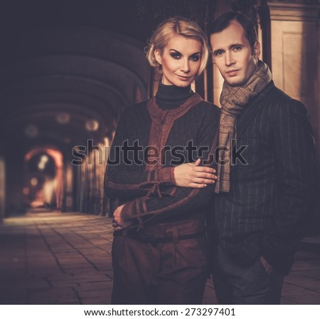Cheerful couple in smart casual wear outdoors at night
