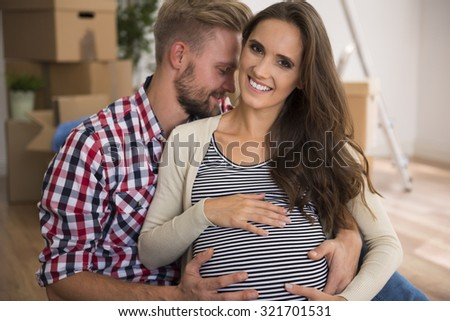 Cheerful couple in their freshly painted apartment - stock photo