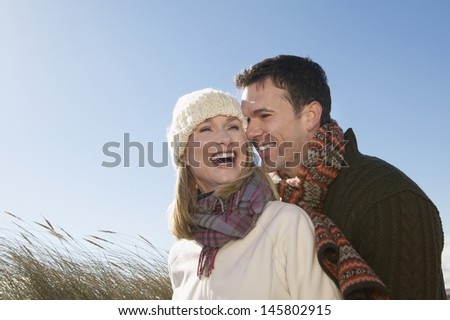 Cheerful couple in winter clothing embracing outdoors