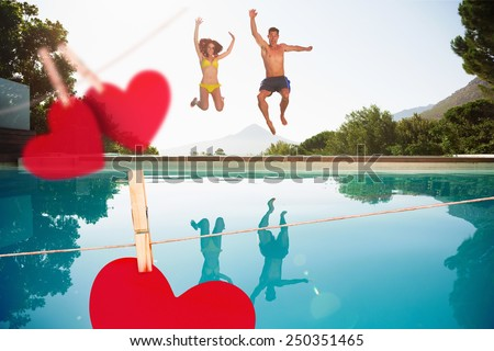 Cheerful couple jumping into swimming pool against hearts hanging on a line - stock photo