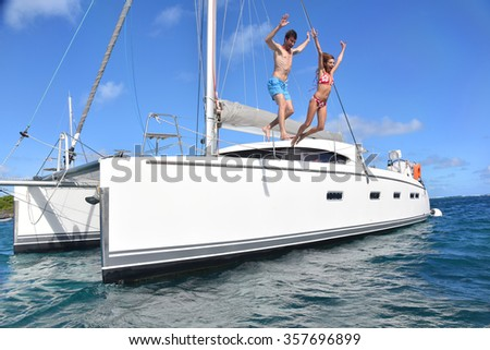 Cheerful couple jumping into water from boat - stock photo