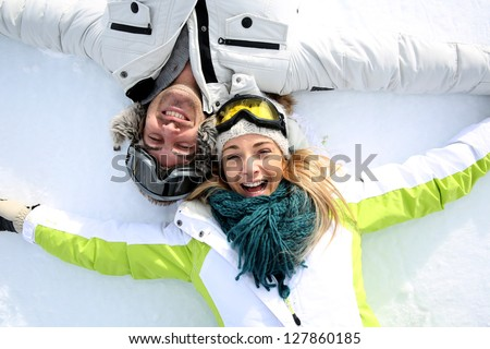 Cheerful couple laying down in snow - stock photo