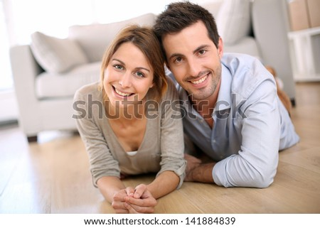 Cheerful couple laying on the floor at home - stock photo